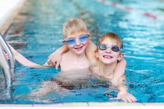 Two kids swimming in the pool. Happy children, twin teenagers boys in swimming goggles, having fun in the pool training before competition Royalty Free Stock Images