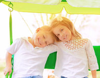 Two kids on swing Stock Photo