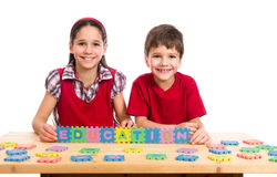 Two kids at the table with puzzle letters Stock Photos