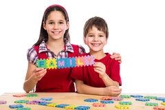 Two kids at the table with puzzle letters Royalty Free Stock Photo