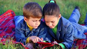 Two kids with tablet PC. Two smiling kids playing with tablet pc on the autumn landscape, outdoors stock video