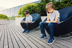 Two kids with tablet and smart phone in the city outdoors. stock photo