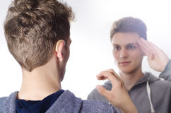 Two kids talking sign language, white background. Selective focus on hearing aid stock photography