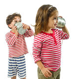Two kids talking on a tin phone. Boy and girl talking on a tin phone isolated on white Royalty Free Stock Image