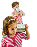 Two kids talking on a tin phone. Boy and girl talking on a tin phone isolated on white stock photos