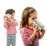Two kids talking on a tin phone. Boy and girl talking on a tin phone isolated on white Royalty Free Stock Images