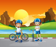 Two kids with their bikes standing at the road near the river Royalty Free Stock Photos