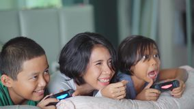 Two kids and their mother playing video game. JAKARTA, Indonesia - June 05, 2018: Slow motion of two happy kids playing video game together with their mother in stock video footage