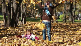 Two kids throw leaves. Two little girls throw fall leaves into air stock video footage