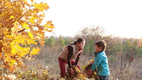 Two kids throwing autumn leaves stock video
