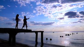 Two kids throwing the stones to sea. On summer sunset stock video footage