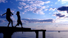 Two kids throwing the stones to sea. On summer sunset, slow motion stock video footage
