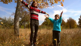 Two kids throwing up the autumn leaves, slow motion stock video footage