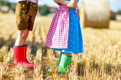 Two kids in traditional Bavarian costumes and red and green rubb. Er boots in wheat field. German children during Oktoberfest . Boy and girl at hay bales during Stock Image