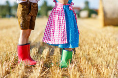 Two kids in traditional Bavarian costumes and red and green rubber boots in wheat field Royalty Free Stock Photo