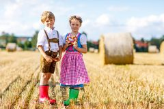 Two kids, boy and girl in traditional Bavarian costumes in wheat field. Two kids in traditional Bavarian costumes in wheat field. German children eating bread Stock Photography