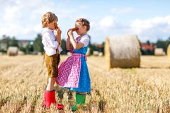 Two kids, boy and girl in traditional Bavarian costumes in wheat field. Two kids in traditional Bavarian costumes in wheat field. German children eating bread Royalty Free Stock Photography