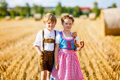 Two kids, boy and girl in traditional Bavarian costumes in wheat field. Two kids in traditional Bavarian costumes in wheat field. German children eating bread Stock Photo