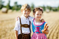 Two kids, boy and girl in traditional Bavarian costumes in wheat field. Two kids in traditional Bavarian costumes in wheat field. German children eating bread Royalty Free Stock Image