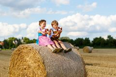 Two kids, boy and girl in traditional Bavarian costumes in wheat field. Two kids in traditional Bavarian costumes in wheat field. German children eating bread Royalty Free Stock Photo