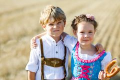 Two kids in traditional Bavarian costumes in wheat field. German children eating bread and pretzel during Oktoberfest stock images