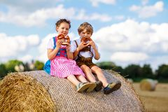 Two kids, boy and girl in traditional Bavarian costumes in wheat field. Two kids in traditional Bavarian costumes in wheat field. German children eating bread royalty free stock images