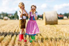 Two kids in traditional Bavarian costumes in wheat field. German children eating bread and pretzel during Oktoberfest. Boy and girl play at hay bales during stock photography