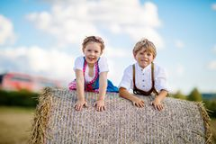 Two kids, boy and girl in traditional Bavarian costumes in wheat field Stock Photos