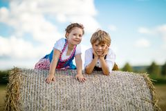 Two kids, boy and girl in traditional Bavarian costumes in wheat field. Two kids in traditional Bavarian costumes in wheat field. German children sitting on hay Stock Images