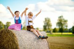 Two kids, boy and girl in traditional Bavarian costumes in wheat field. Two kids in traditional Bavarian costumes in wheat field. German children sitting on hay Royalty Free Stock Image