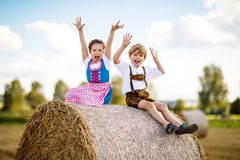 Two kids, boy and girl in traditional Bavarian costumes in wheat field with hay bales. Two kids in traditional Bavarian costumes in wheat field. German children Stock Images