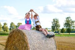 Two kids, boy and girl in traditional Bavarian costumes in wheat field with hay bales. Two kids in traditional Bavarian costumes in wheat field. German children Stock Image