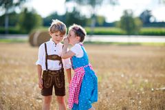 Two kids, boy and girl in traditional Bavarian costumes in wheat field with hay bales. Two kids in traditional Bavarian costumes in wheat field. German children Stock Photography