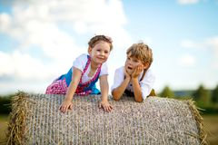 Two kids, boy and girl in traditional Bavarian costumes in wheat field with hay bales. Two kids in traditional Bavarian costumes in wheat field. German children Stock Photo