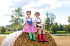 Two kids, boy and girl in traditional Bavarian costumes in wheat field. Two kids in traditional Bavarian costumes in wheat field. German children sitting on hay Stock Photography