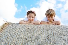 Two kids, boy and girl in traditional Bavarian costumes in wheat field with hay bales. Two kids in traditional Bavarian costumes in wheat field. German children Royalty Free Stock Photography