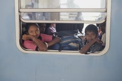 Two Kids On The Train. Two Sri Lanka kids looking out of the window of the train from Ella to Kandy, picture taken at the Nuwara Eliya railway station stock images