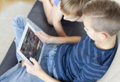 Two kids using tablet at home. Brothers with tablet computer in light room. Boys playing games on tablet pc, emotions. Two blonde kids using tablet at home royalty free stock images