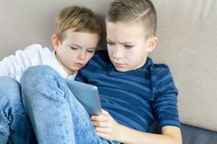 Two kids using tablet pc at home, modern education technology. Brothers with tablet computer in light room. stock photo