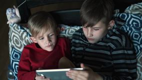 Two kids using tablet pc at home at night. Brothers with tablet computer in dark room. Children, boys playing games on tablet Pc stock footage