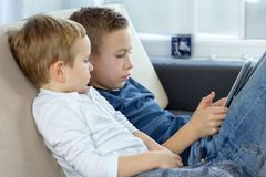 Two kids using touchscreen tablet at home, modern education technology. Brothers with tablet computer in light room. stock image