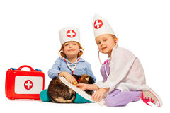 Two kids-veterinarians tie up paw bandage to cat Stock Images