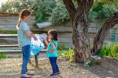 Kids cleaning in park.Volunteer children with a garbage bag cleaning up litter, putting plastic bottle in recycling bag. royalty free stock photo
