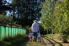 Two kids walk grandfather Stock Image