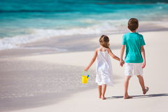 Two kids walking along a beach at Caribbean Stock Photography