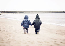 Two kids. Walking on a beach holding hands Royalty Free Stock Photos