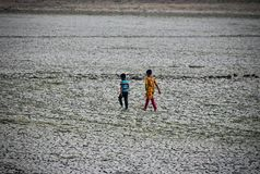Two kids are walking in a cracked soil surface photograph stock photos