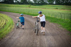 Two kids walking with his bikes on rural landscape Royalty Free Stock Images
