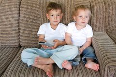 Two kids watching tv Stock Photography