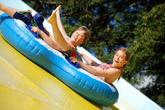 Two kids on water slide. A view of two teenagers on tubes or rafts, enjoying a water slide on a hot summer day. Diagonal perspective stock photos